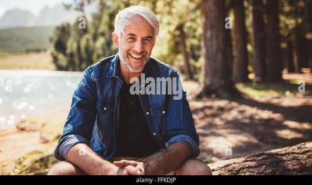 Portrait of happy mature man sitting near a lake looking at camera and smiling. Senior caucasian man sitting on - Stock Image