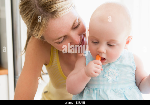 Mother and baby in kitchen eating carrot - Stock Image