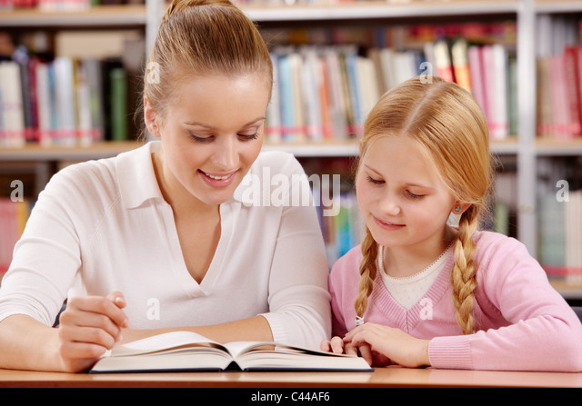 Portrait of schoolgirl and teacher reading interesting book in library - Stock Image