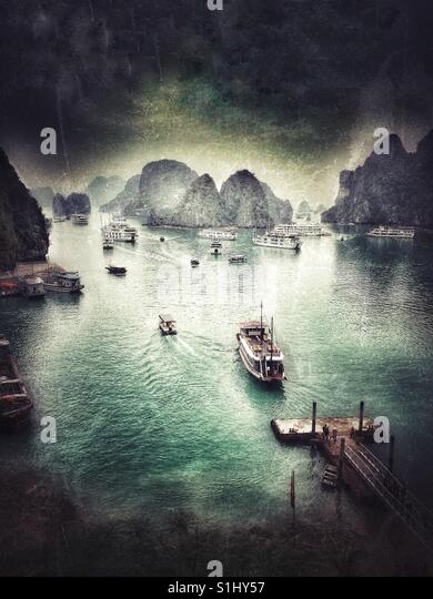 Boats transporting tourists to an island to visit a cave. Halong Bay, Vietnam, South East Asia. - Stock Image