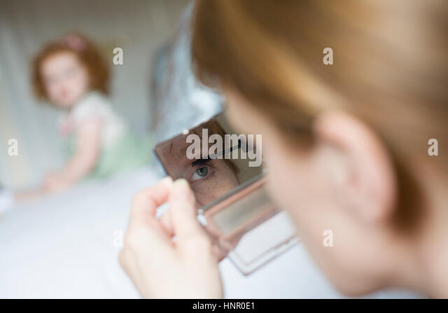 A woman applying make up while her daughter watches - Stock Image
