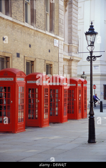 Five traditional British K2 red telephone boxes and a gas streetlamp in Broad Court, Covent Garden, London, England - Stock Image