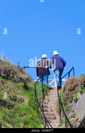 Mature couple reach top of steps by Harbour Master's Office at Porthgain harbour Pembrokeshire Coast National - Stock Image