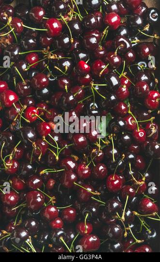 Background of dark red sweet cherries over wooden backdrop - Stock Image