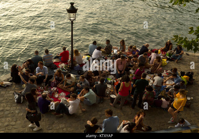 Young people having pic-nick in the early evening on the banks of river Seine, in the île Saint-Louis - Stock Image