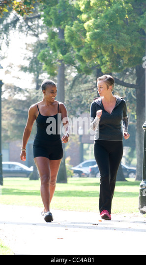 two women exercise together in the park by walking and talking - Stock Image