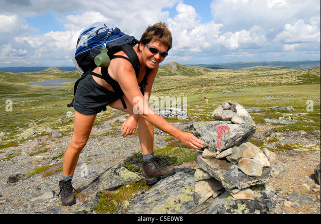 Happy female hiker with backpack reached her goal on mountain landscape against blue sky and clouds - Stock Image