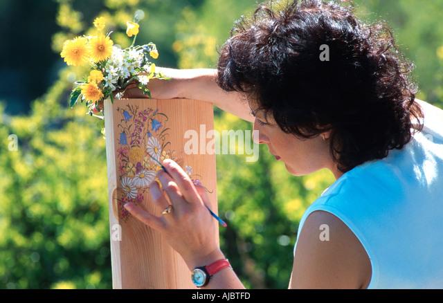 woman painting flowers on board - Stock-Bilder