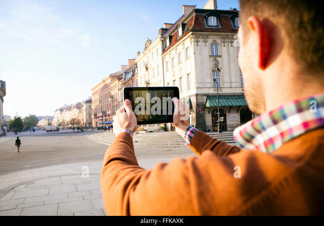 Man on a city break taking a picture with smart phone - Stock Image
