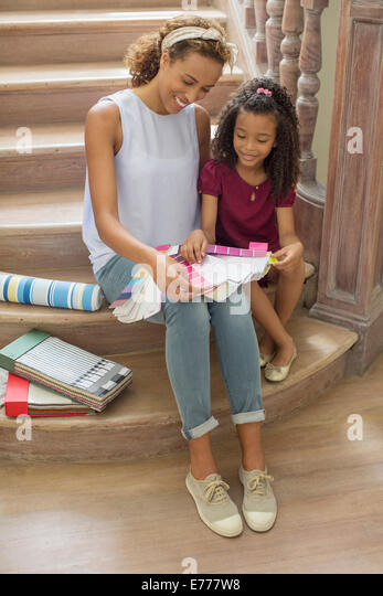 Mother and daughter looking through color swatches together - Stock Image