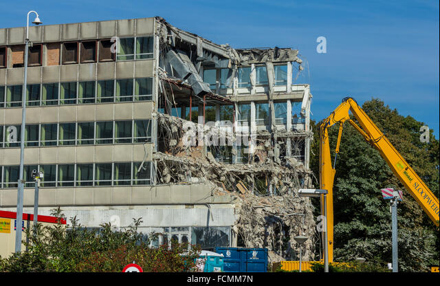 Demolition of a building by a high reach excavator - Stock Image