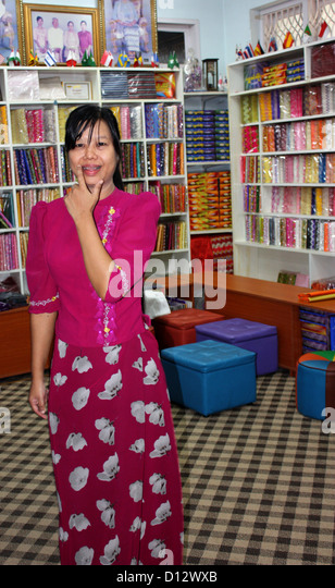 A woman waits for tourists at the showroom of the silk weaving factory in Mandalay (Amarapura Township), Myanmar, - Stock-Bilder