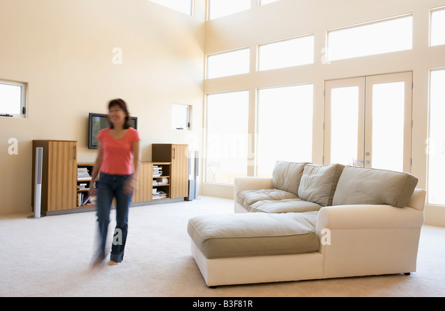 Woman walking through living room - Stock Image