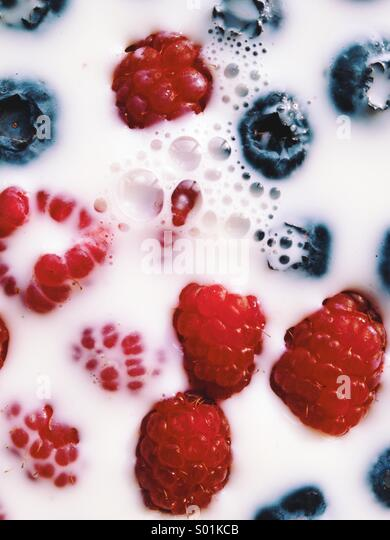 Raspberries and Blueberries in Milk - Stock Image