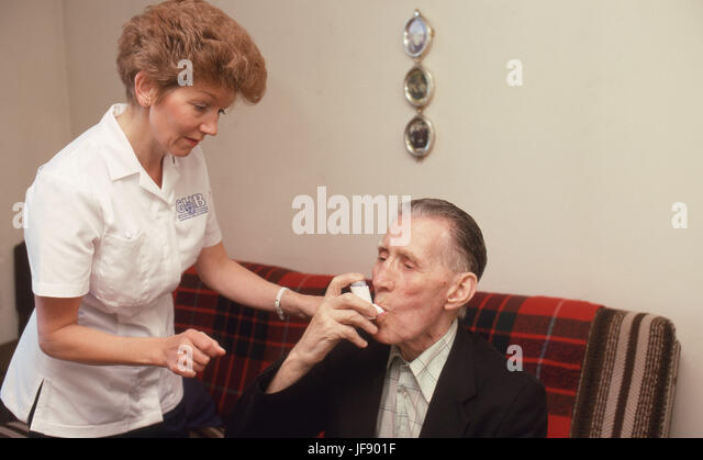 Health visitor assisting elderly man with his asthma medication in sheltered accommodation - Stock Image
