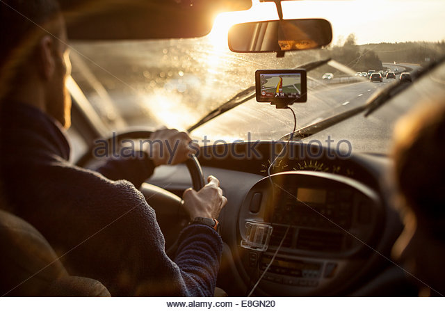 Cropped image of man driving car while using GPS by daughter - Stock Image