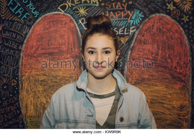 Portrait confident Caucasian tween girl with hair bun against wall with chalk wings - Stock Image