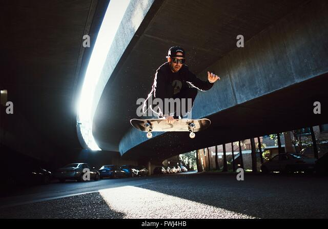 Low Angle View Of Man Jumping On Skateboard - Stock-Bilder