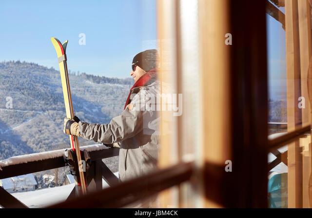 Male skier with skis on sunny cabin balcony - Stock-Bilder