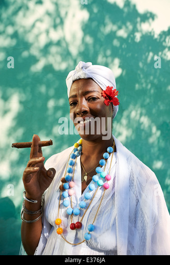 Portrait of african cuban woman smoking cohiba cigar and looking at camera smiling - Stock Image