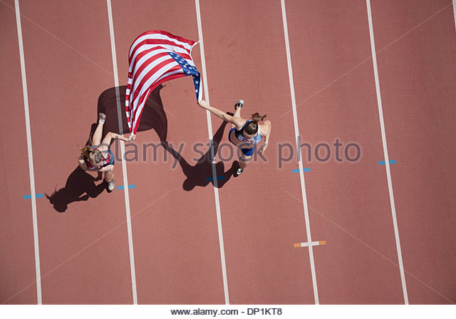 Runners celebrating on track with American flag - Stock-Bilder