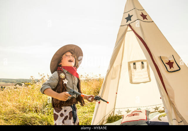 A young boy plays cowboys and indians outside in the sunshine - Stock Image