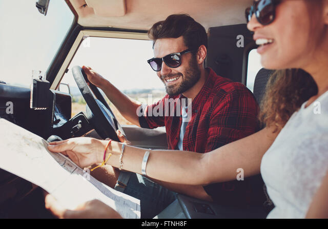 Smiling young man driving the car with woman holding a road map. Young couple on road trip. - Stock Image