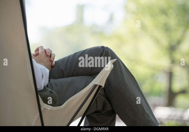 City life. A man sitting in a canvas camping chair in the park. - Stock Image