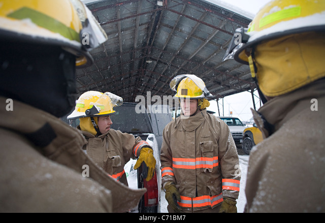 firefighters encircle another firefighter who is talking - Stock Image