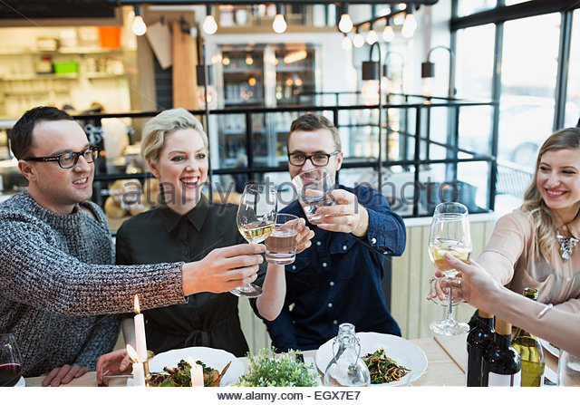 Friends toasting wine glasses at restaurant table - Stock Image
