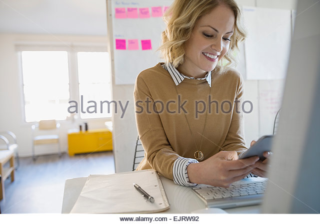 Smiling businesswoman text messaging in conference room - Stock Image