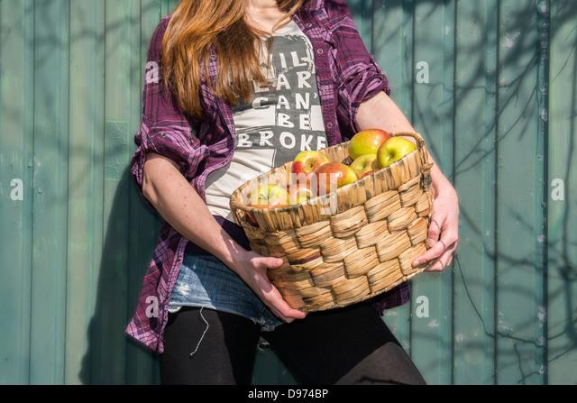 Germany, Teenage girl holding basket with organic apples - Stock Image