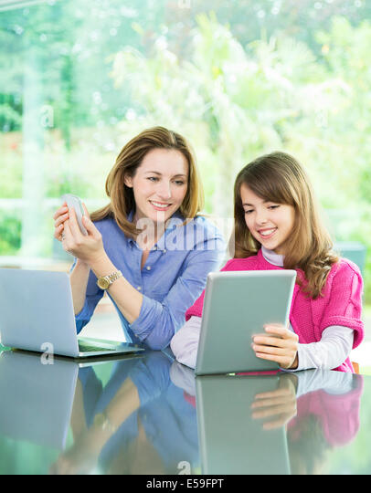 Mother and daughter using technology - Stock Image
