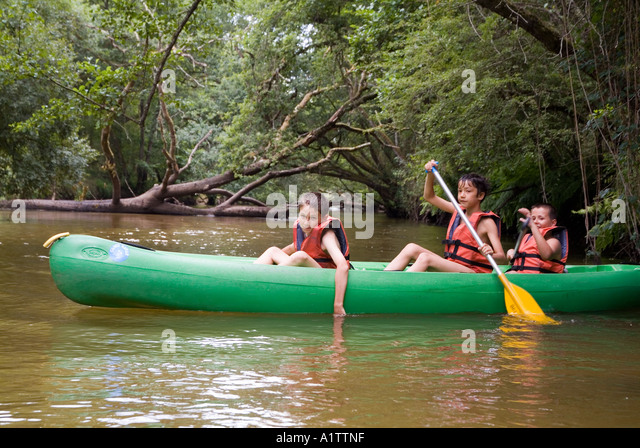 Three boys canoeing in the river Eyre river France - Stock Image
