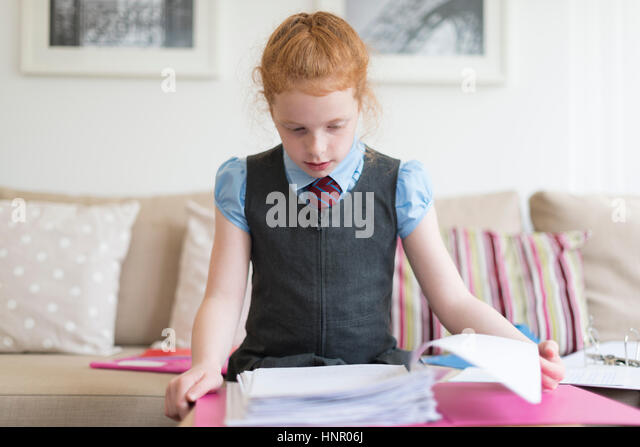A little girl completing her homework. - Stock Image