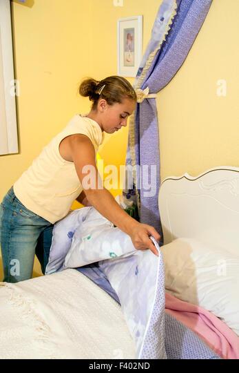 Brazilian American teen girl making her bed.   MR ©Myrleen Pearson - Stock-Bilder