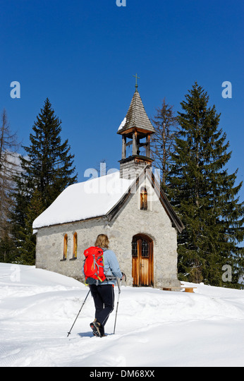 Hiker in winter on the Hemmersuppenalm alpine pasture at St. Anna's Chapel on the way to Fellhorn Mountain, Reit - Stock Image
