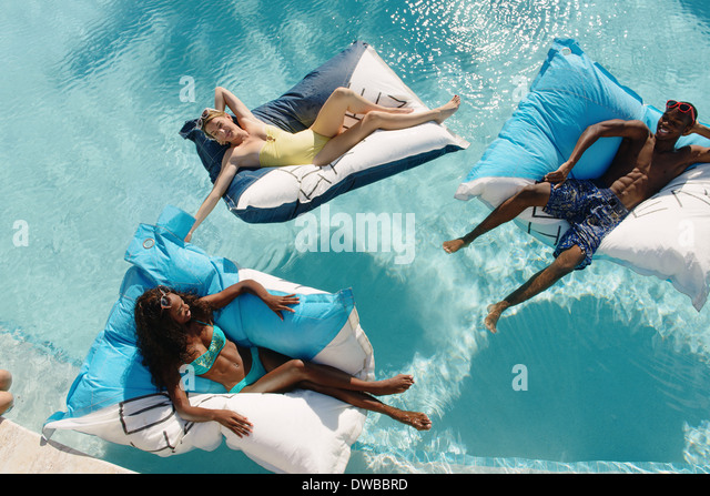Three young adults reclining on airbeds in swimming pool, Providenciales, Turks and Caicos Islands, Caribbean - Stock Image