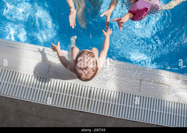 Mother playing with her baby at swimming pool indoor. He reaches hand for mother and sister - Stock Image