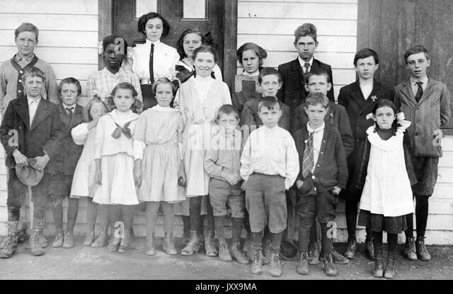 Full length landscape shot of schoolchildren, standing outside building, one African American student, 1920. - Stock Image