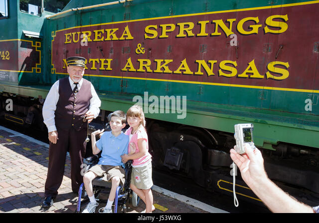 Arkansas Eureka Springs Eureka Springs and North Arkansas Railway conductor man girl boy disabled wheelchair passenger - Stock Image