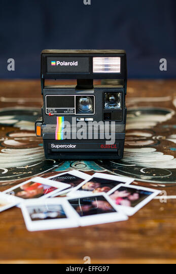 Instant camera and photographs on wooden table - Stock Image