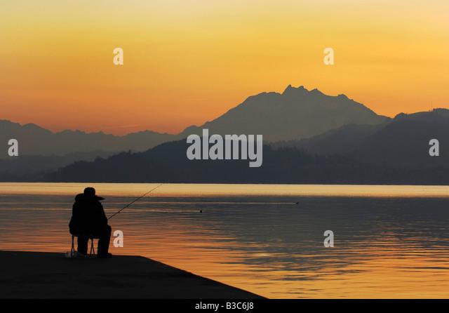 Fisherman at sunset Zug Switzerland - Stock Image
