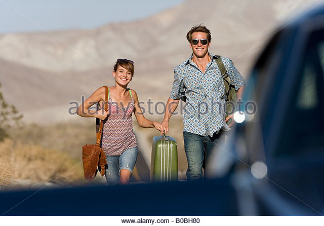Young couple hitchhiking on open road, walking towards car, smiling, portrait - Stock Image