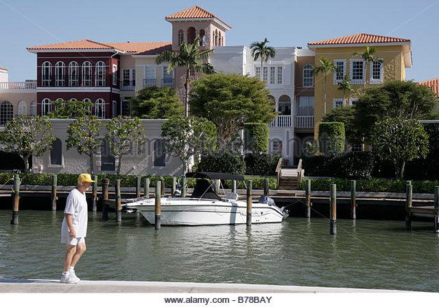 Naples Florida Gulf Shore Boulevard luxury homes townhouses dock waterfront outboard motor boat watercraft man senior - Stock Image
