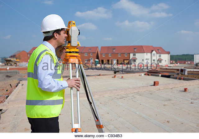 Surveyor using theodolite at construction site - Stock-Bilder