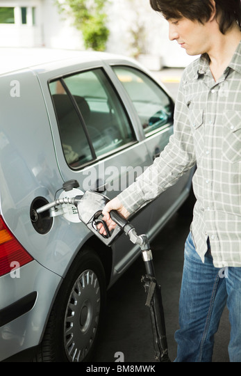 Man refueling car at gas station - Stock Image
