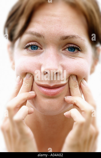 Portrait of young woman pushing up the corners of her mouth to force a smile - Stock Image