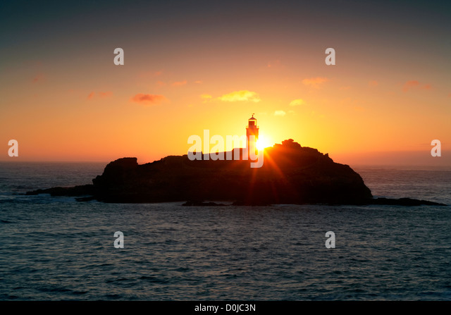 Sunset behind Godrevy Lighthouse on the Cornish coast. - Stock Image
