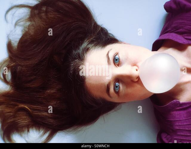 Woman blowing a bubble gum bubble - Stock-Bilder